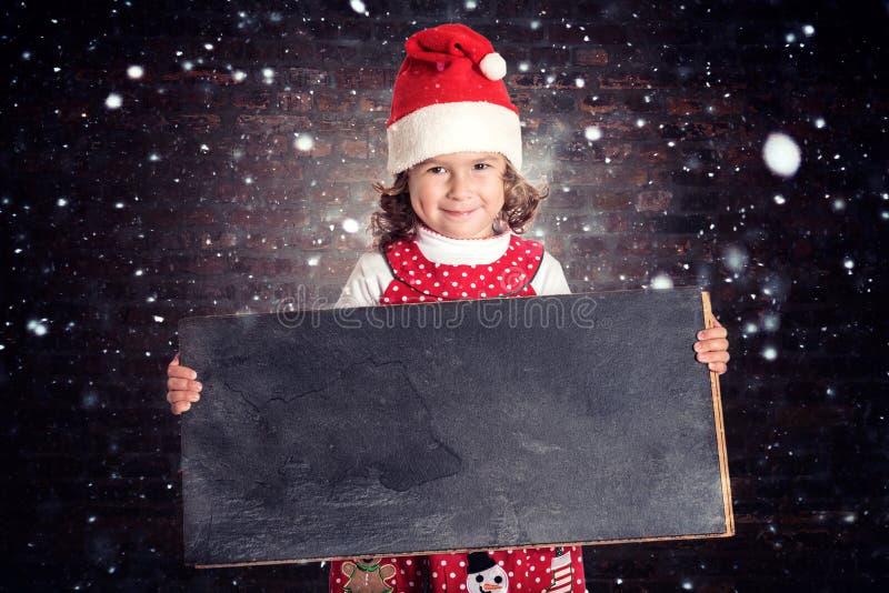 Little girl in Christmas dress holding blackboard. Little positive child holding blank chalkboard,Christmas concept stock images