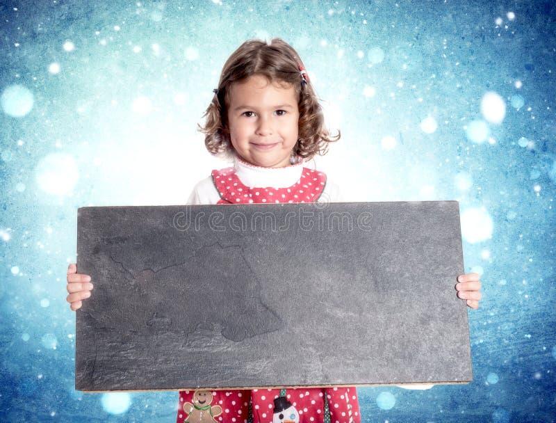 Little girl in Christmas dress. Holding blank chalkboard stock image