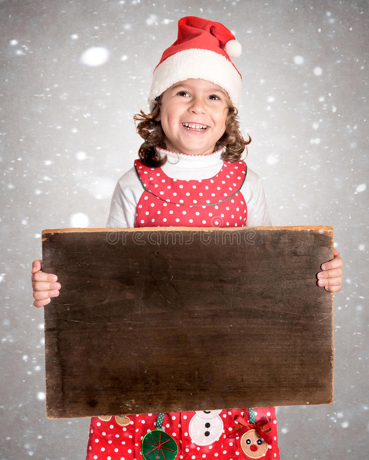 Little girl in Christmas dress holding wooden poster. Little girl in Christmas dress holding blank wooden poster royalty free stock images