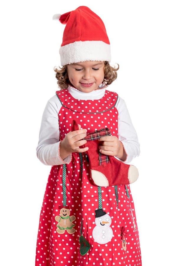 Little girl in Christmas dress. Portrait of positive little child holding Christmas sock,isolated on white background stock image