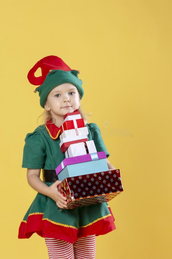 Little girl in a Christmas elf costume, carries a stack of gifts. Photo on a yellow background. stock photography