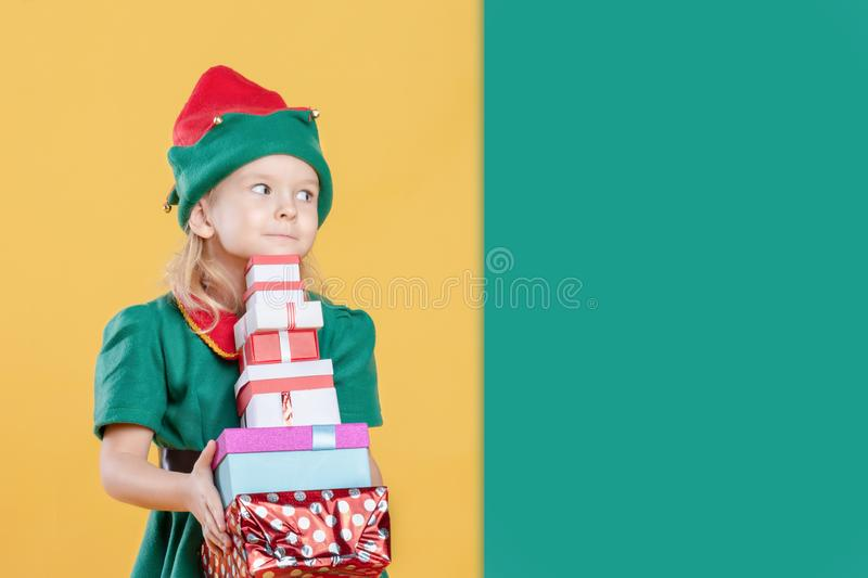 A little girl in a Christmas elf costume holding a stack of gift boxes. Near empty place for text on a green background royalty free stock image