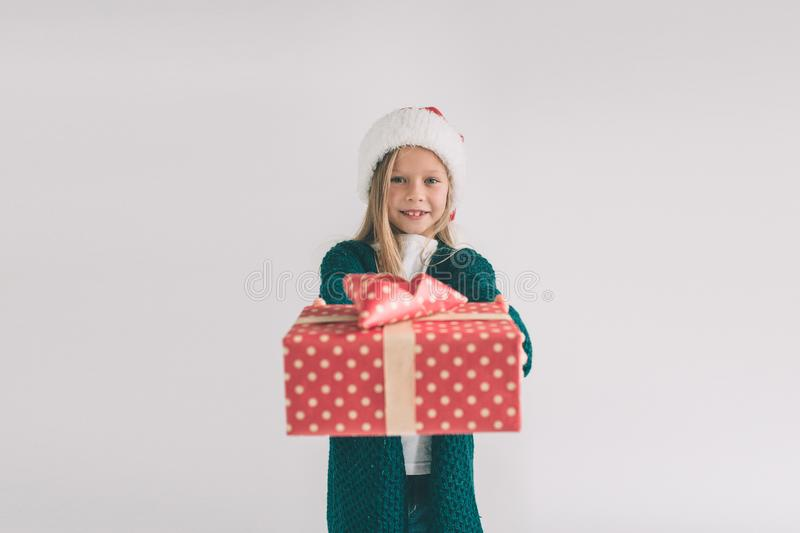 Little girl in a Christmas hat holding gifts on white background. We wish you a Merry Christmas and a Happy New Year. stock images