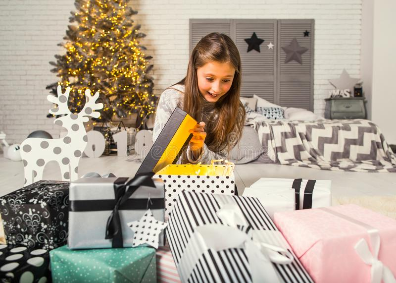 Little girl at christmas opens gifts. Girl at home on christmas looking at gifts under a Christmas tree stock photos