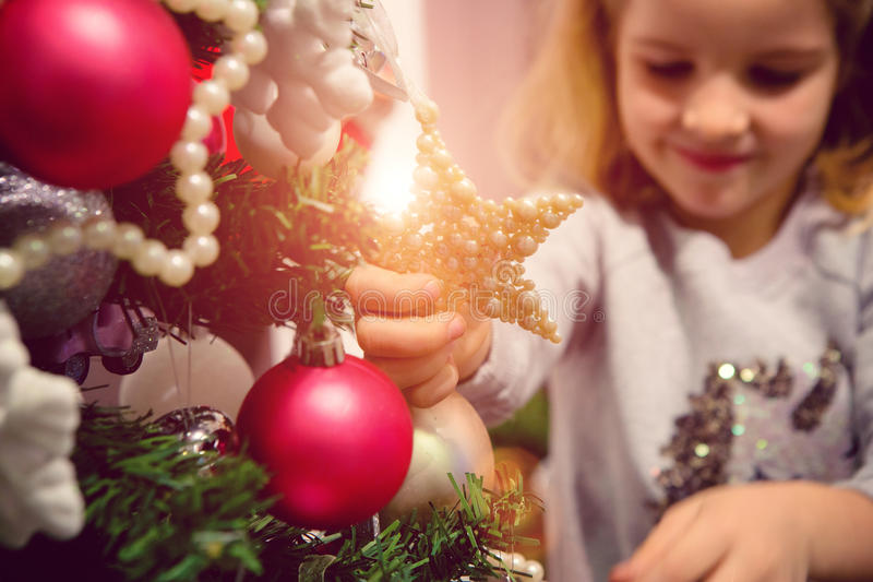 Little girl with Christmas ornaments. Decorating Christmas tree and preparing gifts stock photo