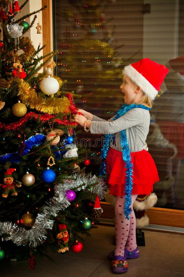 Little girl and christmas tree. Happy, cheerful little girl dressing a Christmas tree stock photos