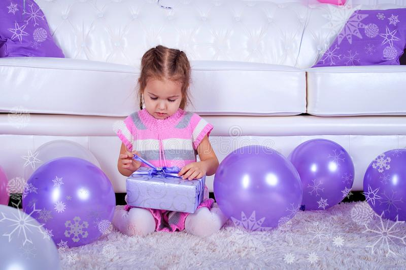 The little girl of Cillit on a floor near a white sofa also opens a lilac gift. Violet balloons royalty free stock photo