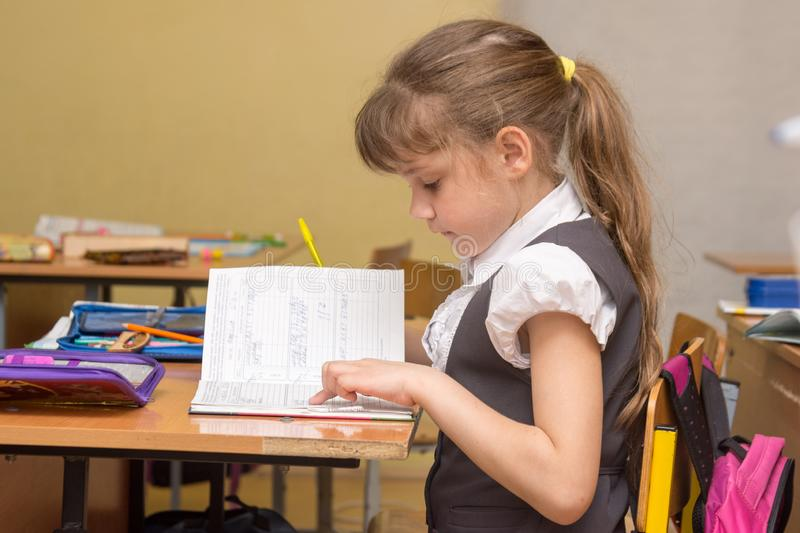 A little girl in class carefully reads a diary entry. A little girl in a class carefully reads a diary entry royalty free stock image
