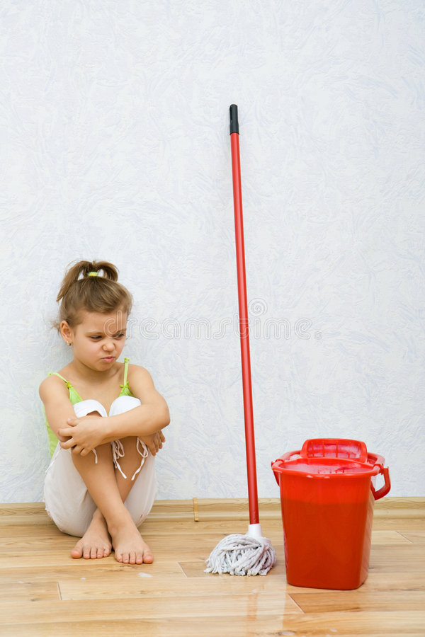 Little girl cleaning the floor royalty free stock photo
