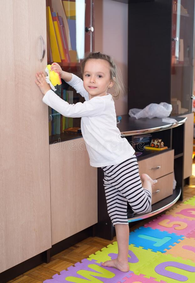Little girl cleaning furniture with a sponge. In her room royalty free stock image