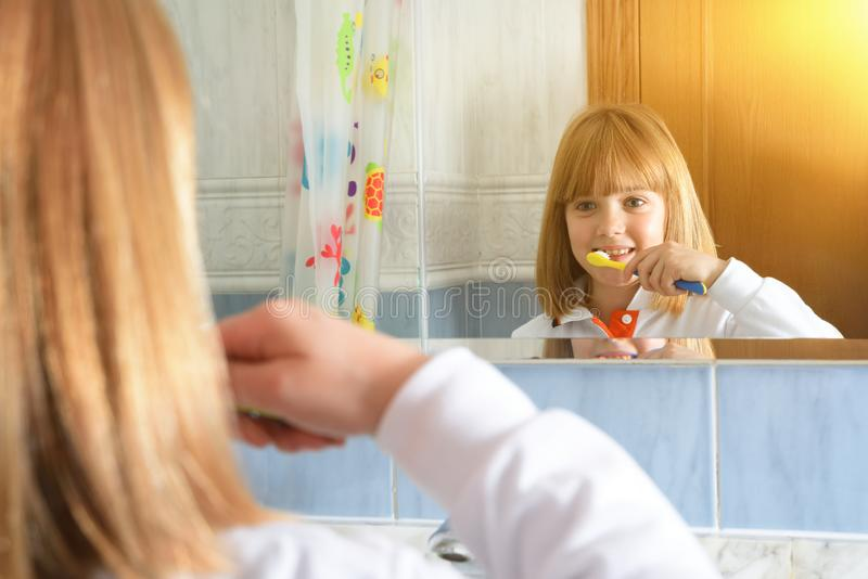 Little girl cleaning her teeth looking at mirror in bathroom stock images