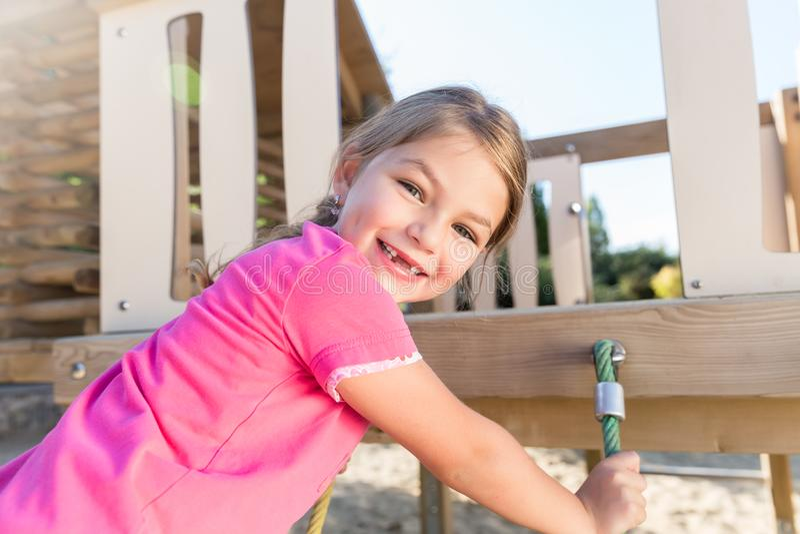 Little girl climbing on adventure playground stock image