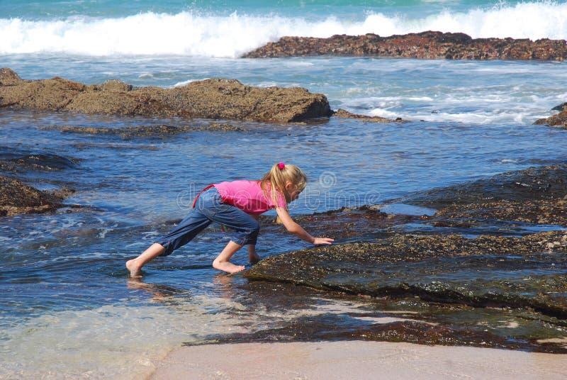 Little girl climbing rocks on beach