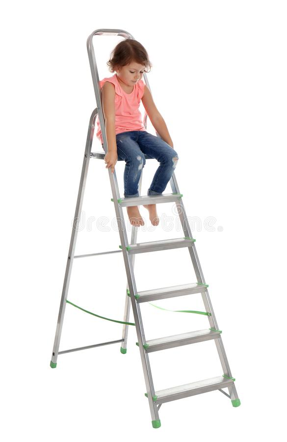 Little girl climbing up ladder on white . Danger at home stock images