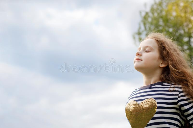 Little girl closed her eyes and breathing with fresh blowing air. stock images