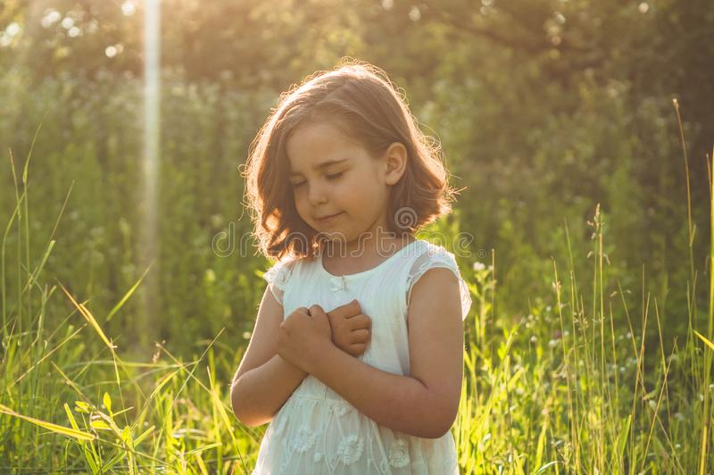 Little Girl closed her eyes, praying in a field during beautiful sunset. Hands folded in prayer concept for faith stock photo