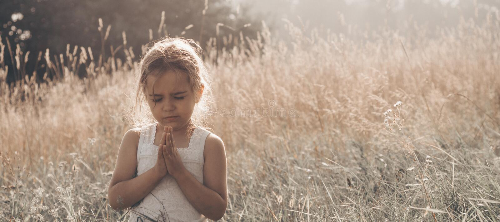 Little girl closed her eyes praying at sunset. Hands folded in prayer concept for faith, spirituality and religion. Hope, concept. royalty free stock image