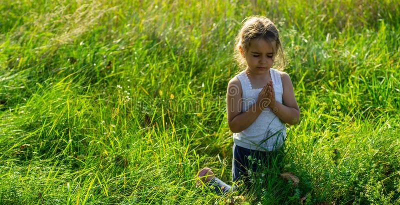 Little girl closed her eyes praying at sunset. Hands folded in prayer concept for faith, spirituality and religion. Hope, concept. royalty free stock photos