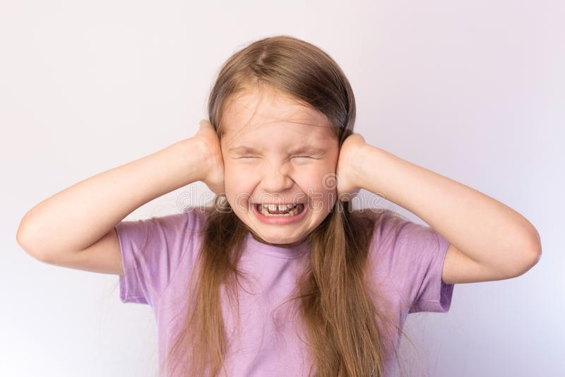 The little girl closed her palms ears, crying, on a light background royalty free stock photos