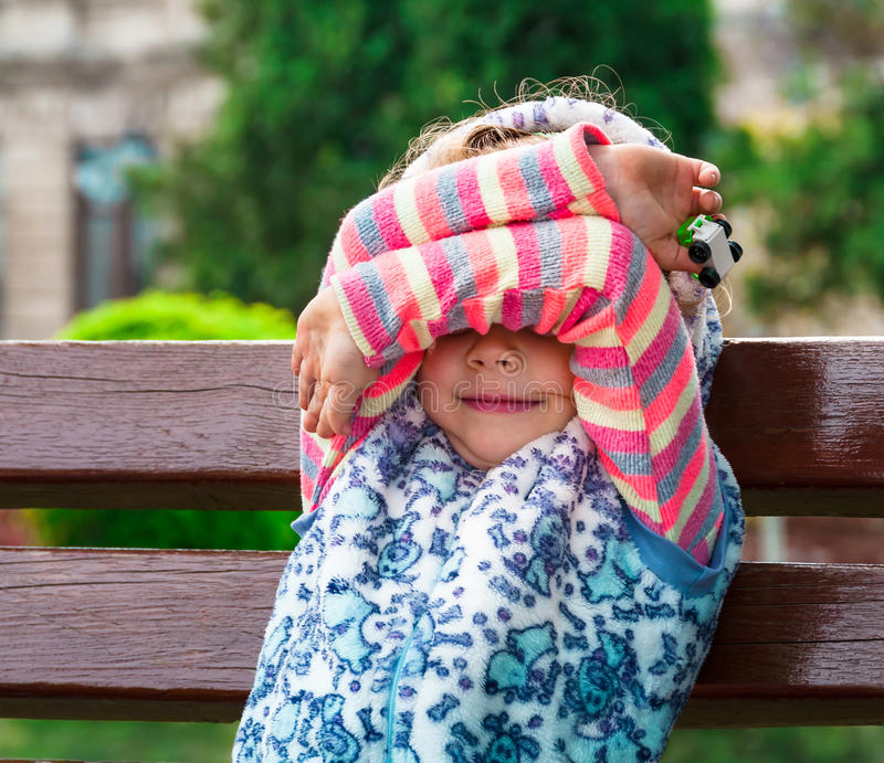 Little girl closes eyes with her hands. stock photography