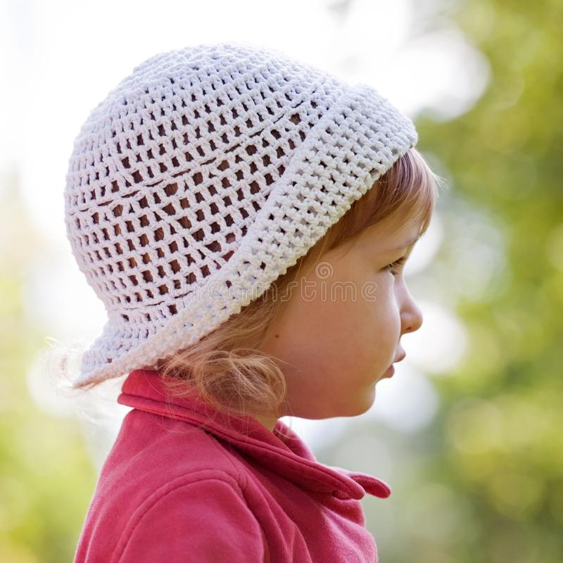 Little girl closeup face in white panama hat side view royalty free stock photo