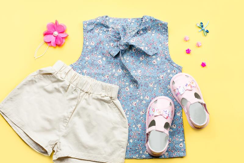 Little girl clothes collection flat lay with blue top, shorts, sandals on pastel background. Top view royalty free stock photo