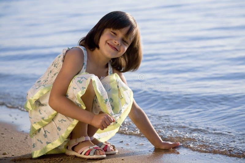 Little girl on coast of sea stock photography