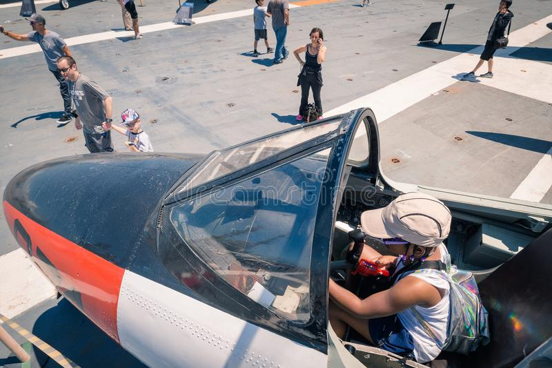 Little Girl in cockpit of plane on the Uss Midway aircraft carrier museum at the San Diego Harbor California clear summer day. The USS midway is a retired stock photos