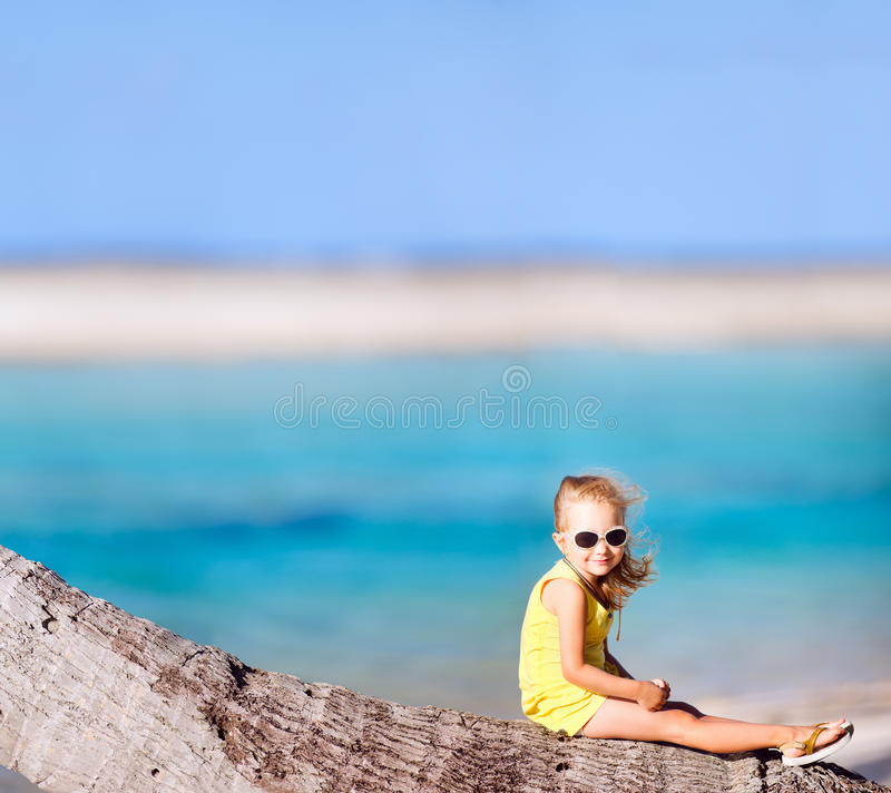 Little girl on coconut palm stock photo