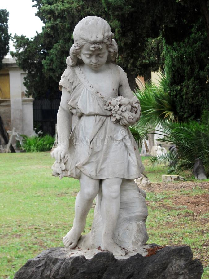 A littke girl collects flowers. A little girl collects flowers. A monument in one of the parks of Cagliari, Sardinia, Italy stock photos