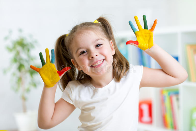 Little girl with color hands in paint stock images