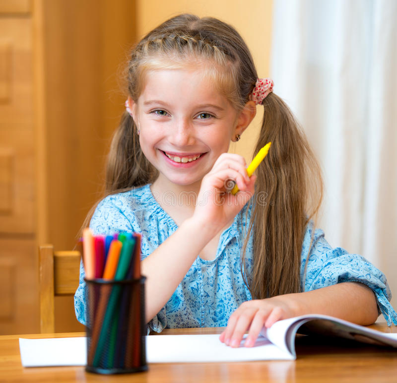 Little girl with colored pencils. Schoolgirl with colored felt-tip pens in the classroom stock photography
