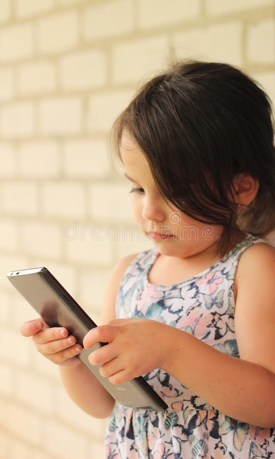 little girl in a colorful dress with a tablet against a brick wall stock photos