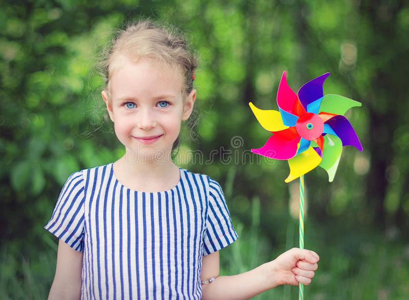 Little girl with colorful pinwheel. royalty free stock photography