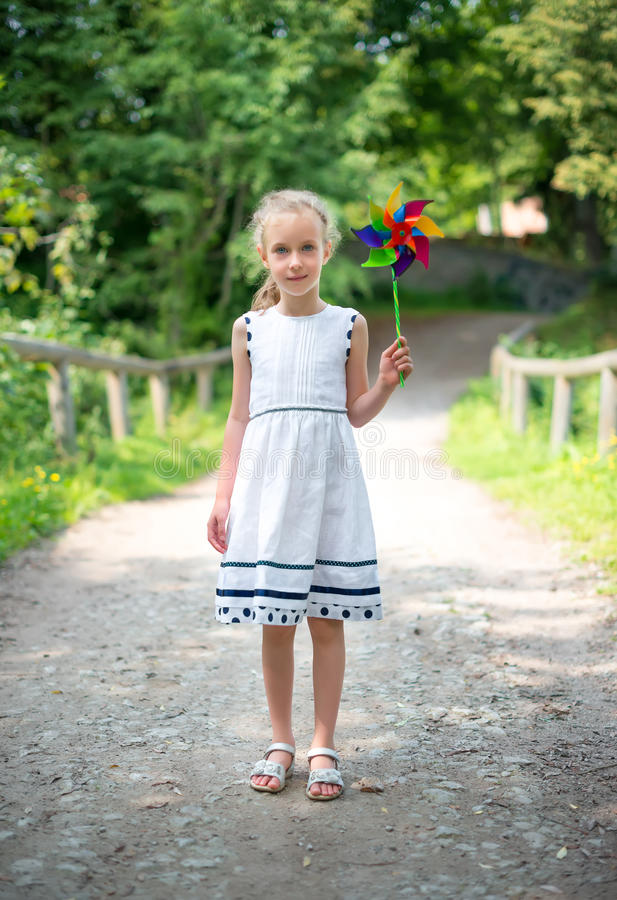 Little girl with colorful pinwheel. royalty free stock images