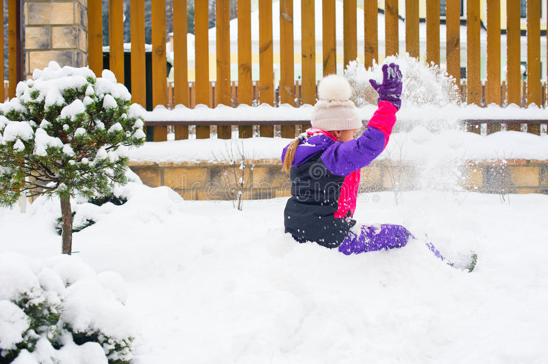Little girl in colorful suit play in snow in back yard in cold w royalty free stock image