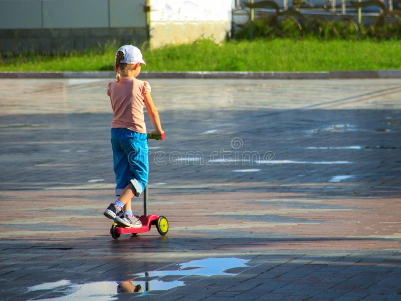 A little girl in colorful summer clothes is riding a children`s scooter among puddles royalty free stock image