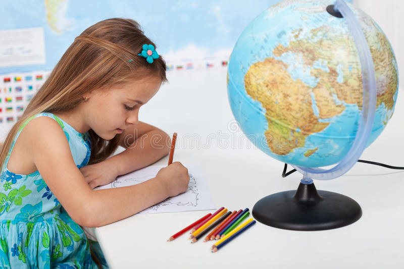 Little girl coloring the world map in geography class royalty free stock photos