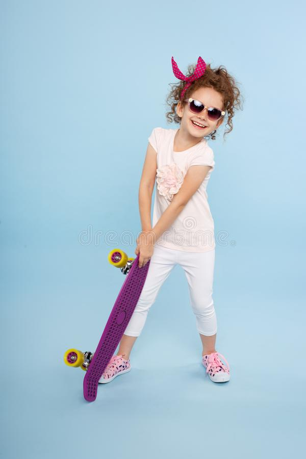 A little girl in a colors clothings and sunglasses, stand and holding a skateboard, isolated on a blue background. royalty free stock photos