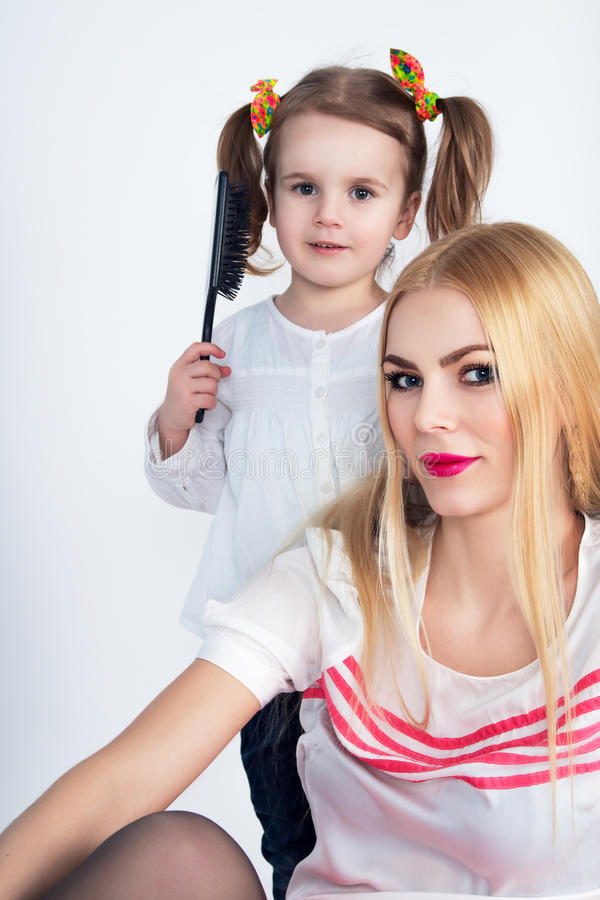 Little girl combing her hair mom royalty free stock images