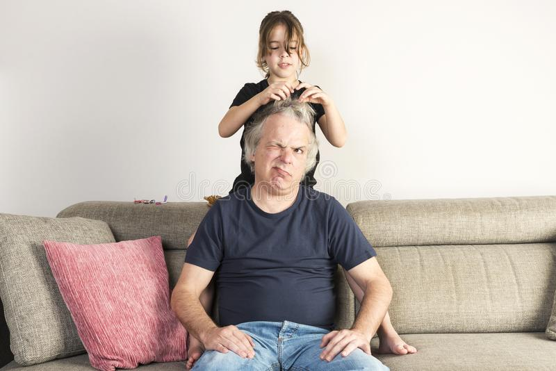 Little girl combing and making pigtails her dad at home royalty free stock photo