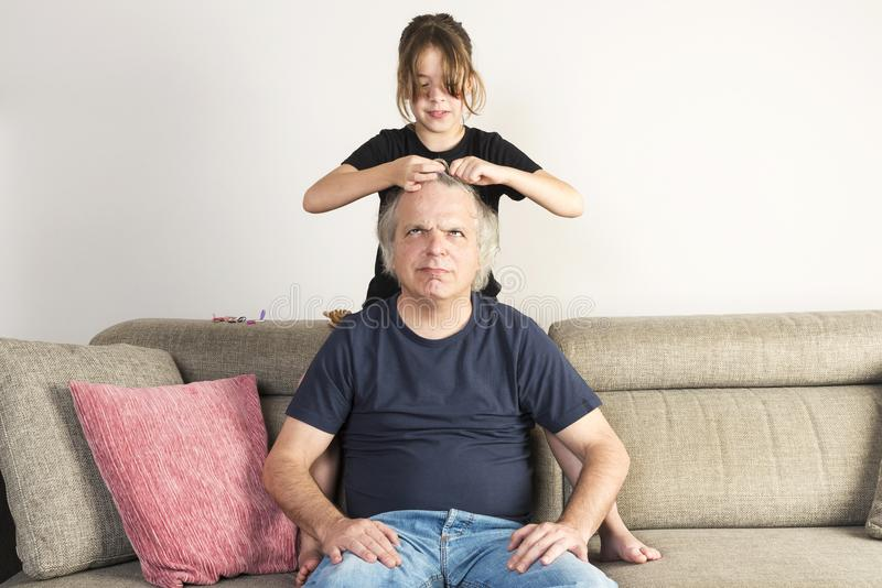 Little girl combing and making pigtails her dad at home stock images