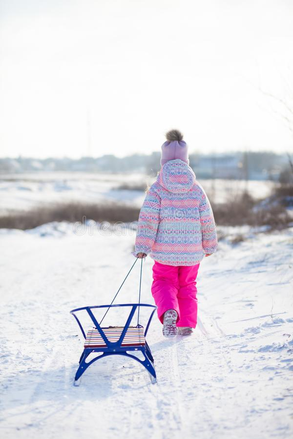 A little girl comes down from a snow slide and pulls a sled royalty free stock image