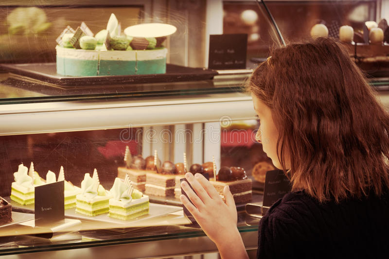 Little girl in confectionary shop looking at the display. Sweet royalty free stock photography