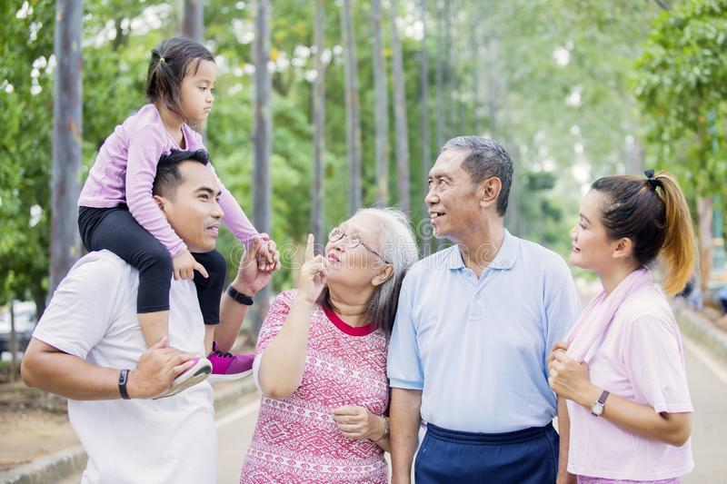 Little girl conversing with her family on the road. Picture of little girl looks happy while conversing with her grandparents and parents on the road stock photos