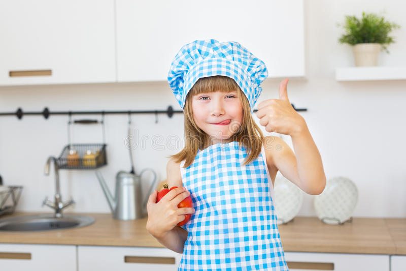 Little girl in cook clothes cuts a bell pepper on a board stock image
