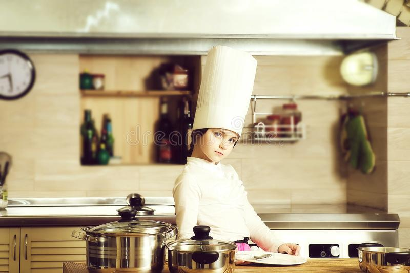 Little girl cook. Cooking, food, study. Small girl with pans and spoons  in cook hat royalty free stock photography