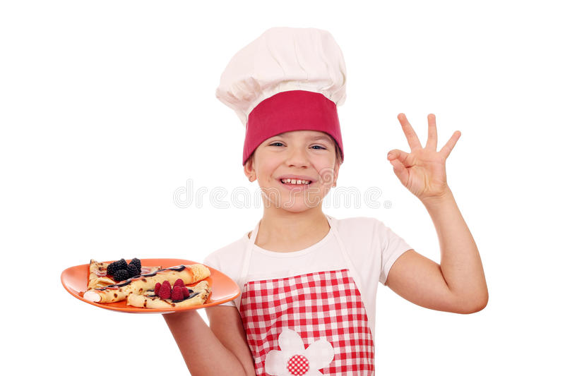 Little girl cook with crepes and ok hand sign. Happy little girl cook with crepes and ok hand sign royalty free stock images