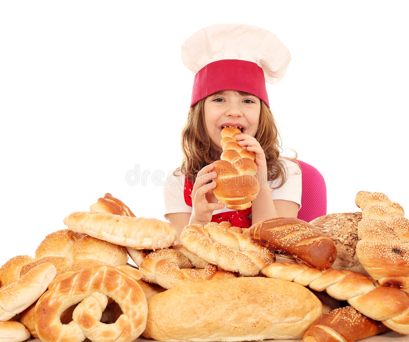Little girl cook eat bread. Hungry little girl cook eat bread stock images