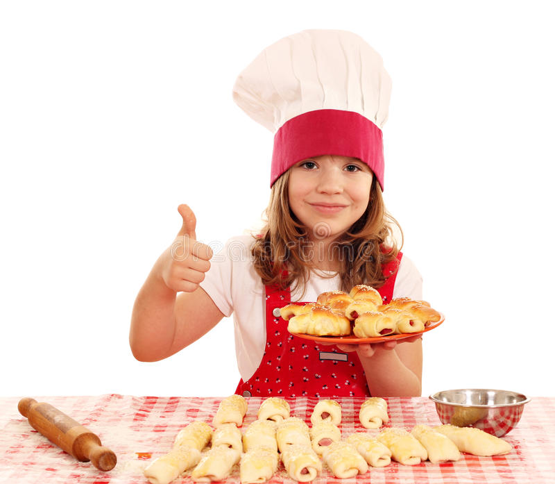 Little girl cook with rolls and thumb up. Happy little girl cook with rolls and thumb up stock images